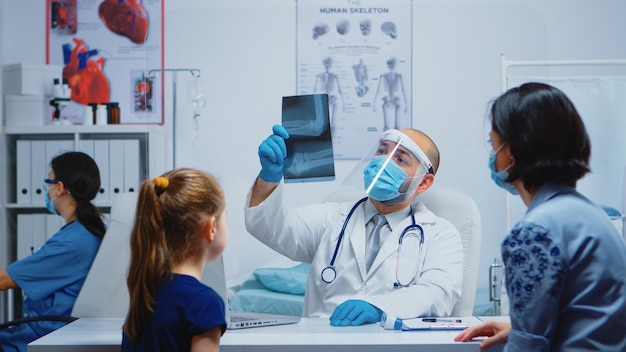 Medizinischer mitarbeiter mit schutzmaske, der die röntgenaufnahme des elternteils während des coronavirus erklärt. facharzt für medizin, der beratung im gesundheitswesen anbietet, röntgenbehandlung im klinikkabinettkrankenhaus