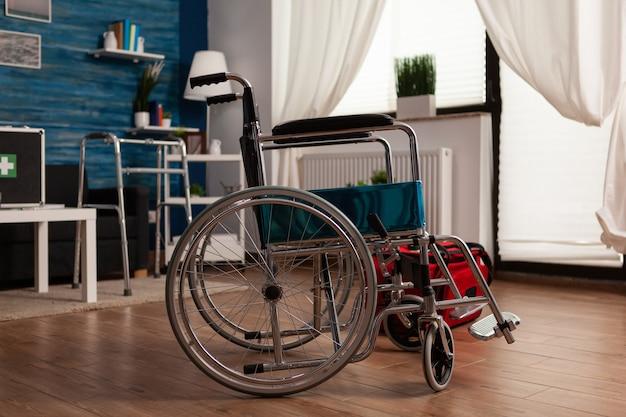 Medizinischer rollstuhl des krankenhauses, der im leeren wohnzimmer mit niemandem darin steht