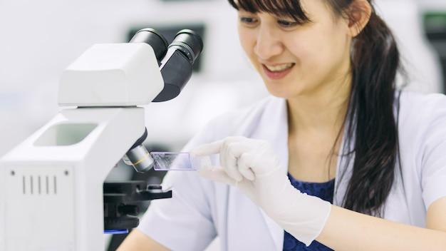 Medizinischer technologe, der im labor unter verwendung eines mikroskops für entdeckungstest arbeitet.