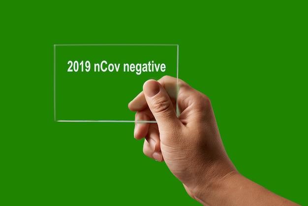 Medizinischer test mit menschlicher hand und negatives ergebnis für 2019 ncov gegen einen grünen backplatz, kopierraum. ausbruch von coronavirus, covid-19 oder pandemiekonzept.