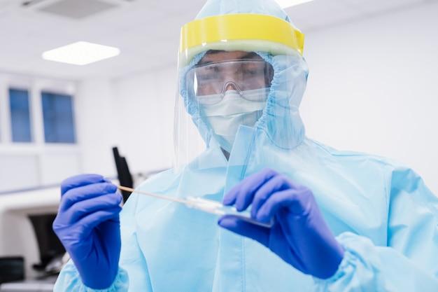 Medizinischer wissenschaftler in psa anzug uniform hält tupfer coronavirus-test im labor