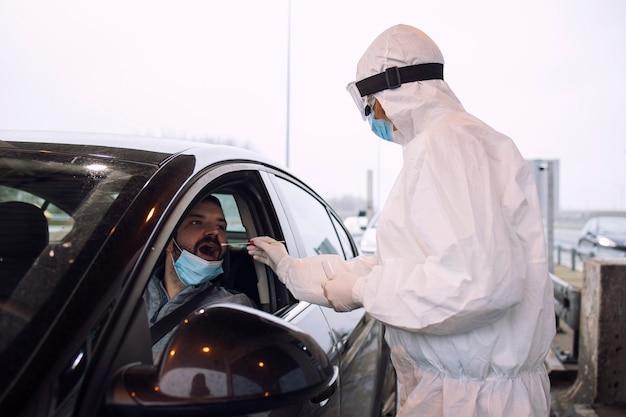 Medizinisches gesundheitspersonal im schützenden weißen anzug mit handschuhen und gesichtsmaske, die nasen- und rachenabstrich nimmt, um passagier auf koronavirus zu testen.