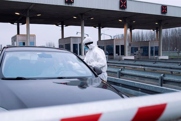 Medizinisches gesundheitspersonal im weißen schutzanzug, das am checkpoint einen nasentupfertest auf coronavirus durchführt.