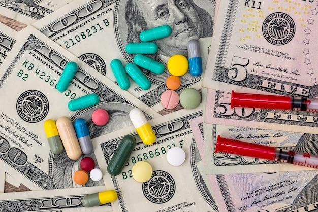 Medizinisches konzept - dollar, pillen und spritzen