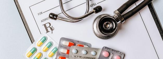 Medizinisches konzept flach lag mit stethoskop, pillen, notizblock auf dem arztdesktop
