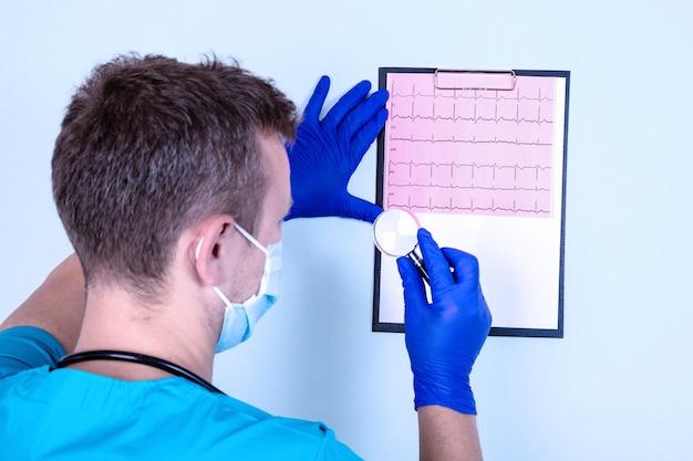 Medizinisches konzept für herzinfarkt. der arzt hält ein kardiogramm.
