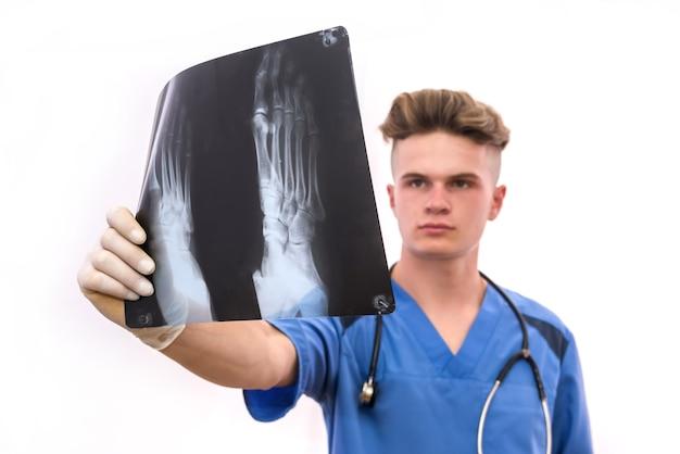 Medizinisches konzept. junger arzt untersucht das röntgenbild des patienten isoliert auf weiß