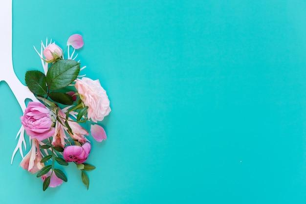 Medizinisches konzept von rosa lila blüten in menschlichen lungen auf blauem hintergrund geformt. entzündung des lungenkonzepts, virusepidemie. flache lage, ansicht von oben. schaden des rauchens