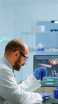 Medizinisches labormaterial, das über die entwicklung von impfstoffen diskutiert, die ein reagenzglas mit blutprobe halten. mediziner arbeiten mit dna-scan-bild in modern ausgestatteten labors mit high-tech
