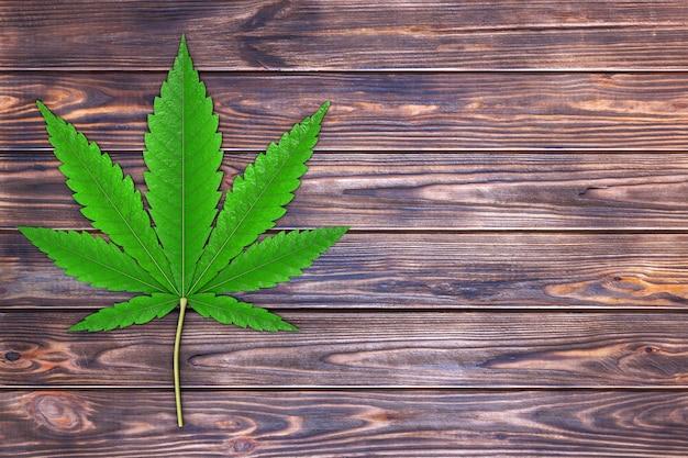 Medizinisches marihuana oder cannabis hanfblatt auf einem brettertisch. 3d-rendering