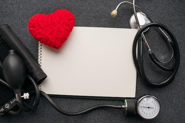 Medizinisches modell. weißes notizbuch, rotes threadherz mit tonometer