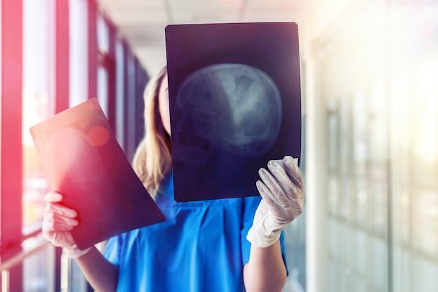 Medizinisches personal betrachtet röntgenfilm des schädels, um anzeichen der krankheit zu erkennen. gesundheit