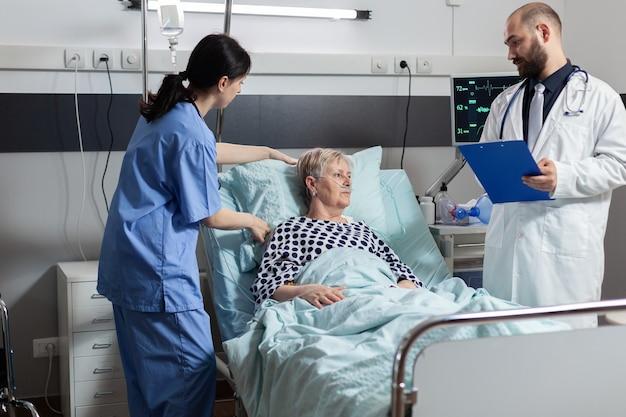 Medizinisches personal, das den gesundheitszustand der älteren frau überprüft
