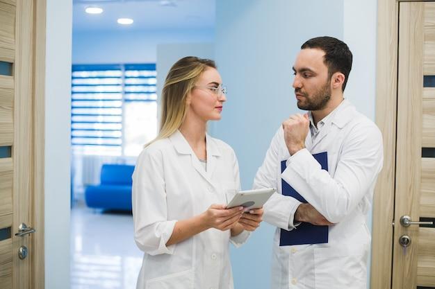 Medizinisches personal, das diskussion im modernen krankenhaus-korridor hat