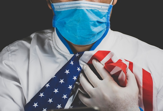 Medizinisches personal, das eine gesichtsmaske trägt und die amerikanische flagge hält