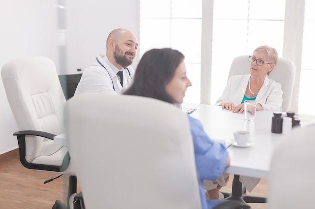Medizinisches personal, das im konferenzraum lächelt, während es mit anderen ärzten spricht, die weißen kittel tragen. kliniktherapeut mit kollegen, die über krankheit, experten, spezialisten, kommunikation sprechen.
