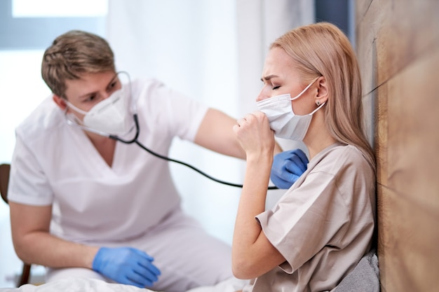 Medizinisches personal, das kranke patienten zu hause untersucht, gesundheitsdienst und medizinische versorgung sowie covid-19-testkonzept. professioneller männlicher arzt verwenden stethoskop. kranke frau husten, konzentrieren sich auf weiblich