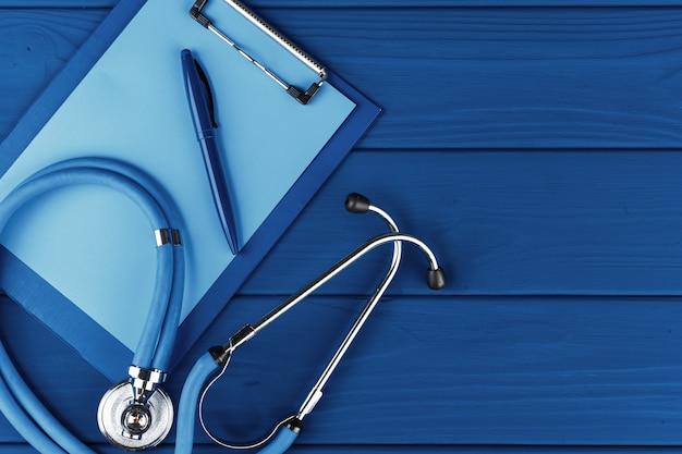 Medizinisches stethoskop auf klassischer blauer tischoberansicht