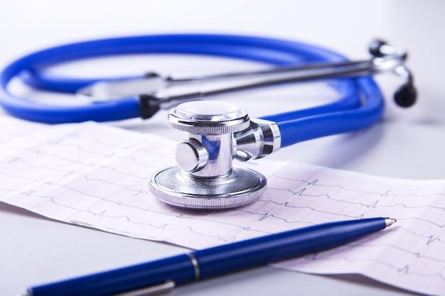 Medizinisches stethoskop, das auf kardiogrammkarte liegt