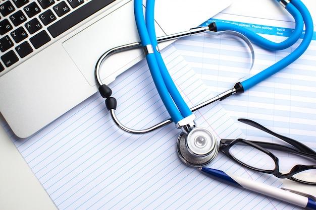 Medizinisches stethoskop mit brille, laptop und stift
