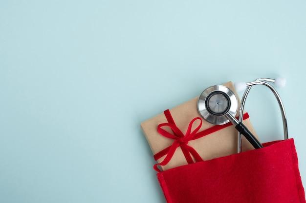 Medizinisches stethoskop mit geschenkbox in der roten tasche des weihnachtsmanns. weihnachts- und neujahrskarte