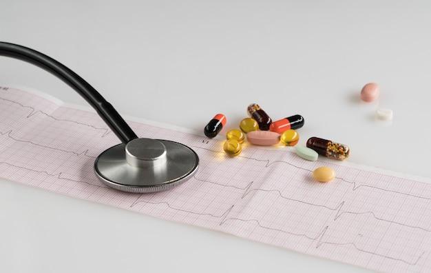 Medizinisches stethoskop mit pillen und kardiogramm auf hellem hintergrund