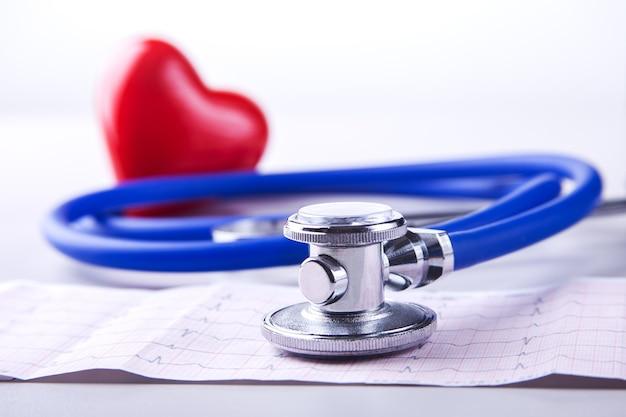 Medizinisches stethoskop und rotes herz, die auf kardiogrammkarte liegen