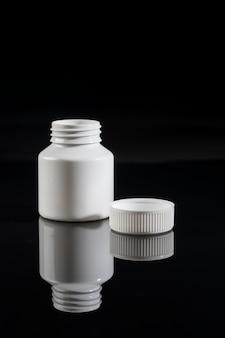 Medizinisches stillleben auf schwarzem hintergrund isoliert. weiße flasche pillen.