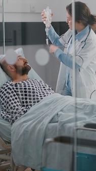 Medizinisches team, das die vitalfunktionen des patienten überwacht, die herzfrequenz überprüft und bei der flüssigkeitszufuhr hilft