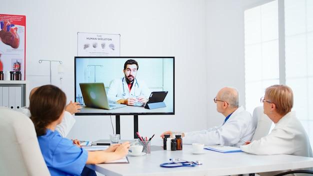 Medizinisches team, das eine online-konferenz im sitzungssaal mit einem facharzt abhält und notizen in der zwischenablage macht. gruppe von ärzten, die die diagnose über die behandlung von patienten mit videoanrufen besprechen
