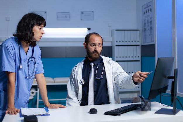 Medizinisches team, das mit computer für behandlung und gesundheitsfürsorge arbeitet