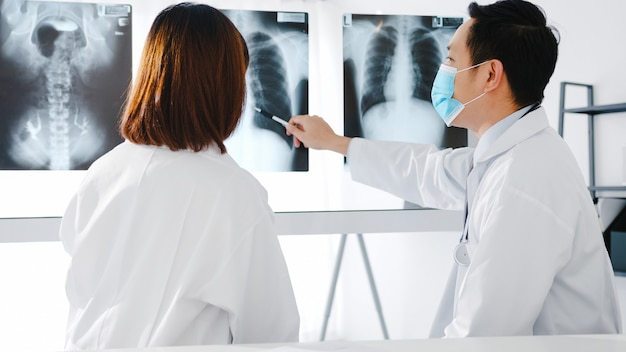 Medizinisches team von asien ernsthafte männliche und junge ärztin mit schützenden gesichtsmasken, die computertomographieergebnisse im krankenhausbüro diskutieren.