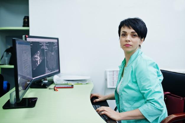 Medizinisches thema. arzt im mri-büro im diagnosezentrum im krankenhaus, sitzend in der nähe von computermonitoren.