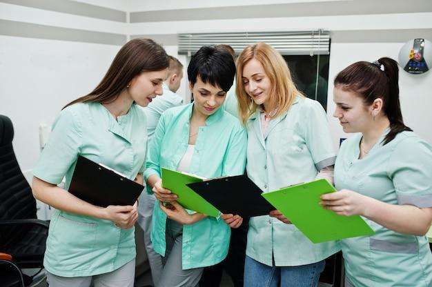 Medizinisches thema. beobachtungsraum mit computertomograph. die gruppe von ärztinnen mit klemmbrettern trifft sich im mrt-büro im diagnosezentrum im krankenhaus.