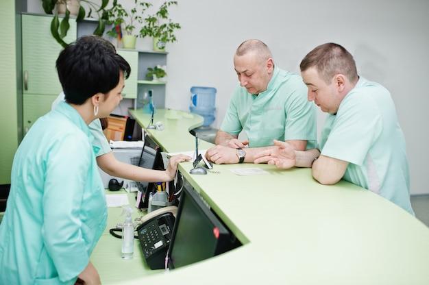 Medizinisches thema. gruppe von ärzten, die sich an der rezeption des diagnosezentrums im krankenhaus treffen.