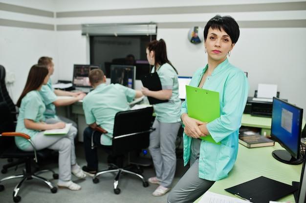 Medizinisches thema. porträt der ärztin mit zwischenablage gegen gruppe von ärzten, die im mri-büro am diagnosezentrum im krankenhaus treffen.