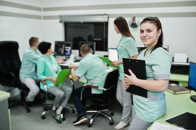 Medizinisches thema. porträt einer ärztin mit zwischenablage gegen eine gruppe von ärzten, die sich im mri-büro im diagnosezentrum im krankenhaus treffen.