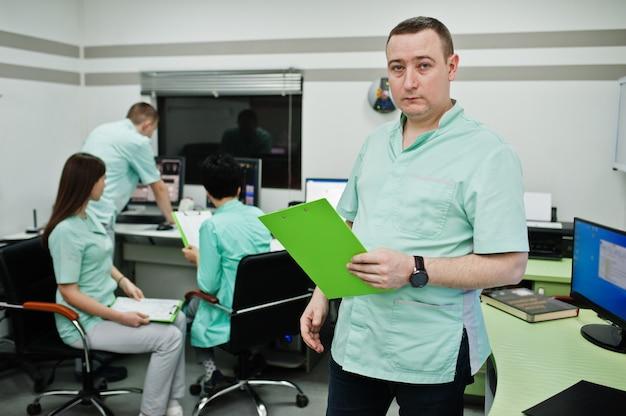 Medizinisches thema. porträt eines männlichen arztes mit zwischenablage gegen eine gruppe von ärzten, die sich im mri-büro im diagnosezentrum im krankenhaus treffen.