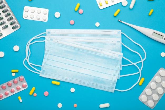 Medizinisches thermometer und maske mit pillen auf blau. coronavirus-prävention. chirurgische maske für covid19