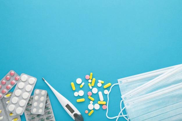 Medizinisches thermometer und maske mit pillen auf blauem hintergrund. coronavirus-prävention. chirurgische maske für covid19
