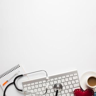 Medizinisches werkzeug und tasse kaffee mit dem genähten spielzeugherzen lokalisiert auf weißem hintergrund