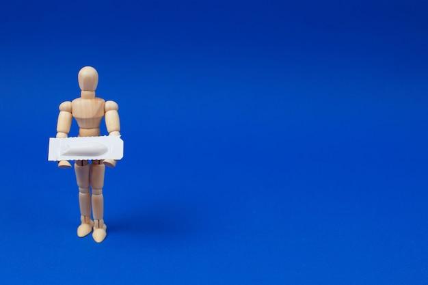 Medizinisches zäpfchen, rektal oder vaginal. hölzerner mann hält medizinisches zäpfchen auf blauem hintergrund.