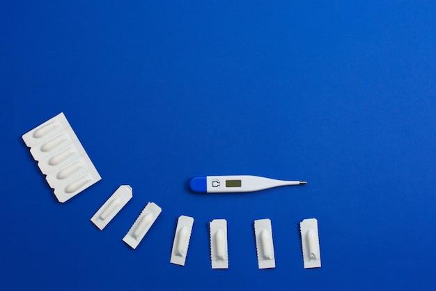 Medizinisches zäpfchen, rektal oder vaginal. isoliert auf blauem hintergrund.