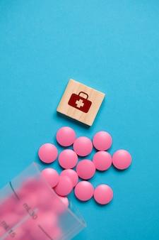 Medizinisches zeichen auf einem holzwürfel neben rosa tabletten von einem plastikbecher