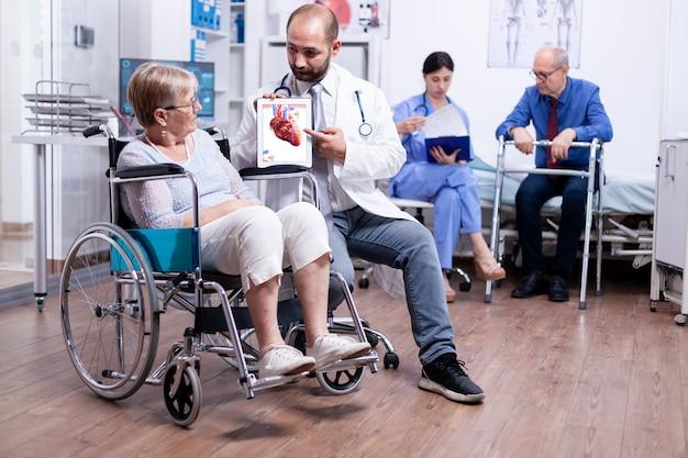 Medizinisches zeug, das einer behinderten älteren frau, die im rollstuhl sitzt, eine broschüre mit arrhythmien präsentiert