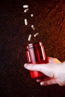 Medizinkapseln für die behandlungskrankheit, die in ein glas fällt