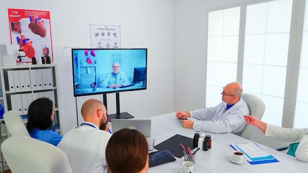 Medizinpersonal, das während des online-meetings eine videokonferenz des krankenhausteams mit einem erfahrenen arzt über das internet hat. ärzte im gespräch mit therapeuten für fachwissen im konferenzbüro.