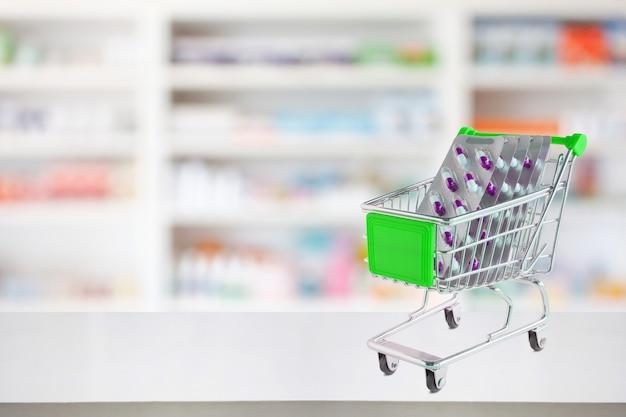 Medizinpillen blisterpackung kapsel im einkaufswagen auf der theke der apotheke mit unscharfen drogerieregalen defokussierten hintergrund