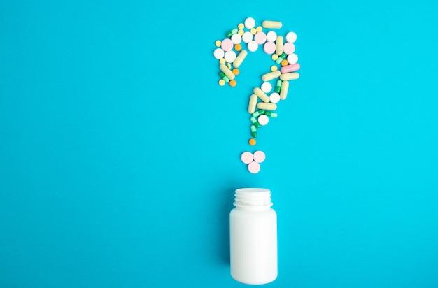 Medizinpillen, tabletten und kapseln und flasche auf blauem hintergrund