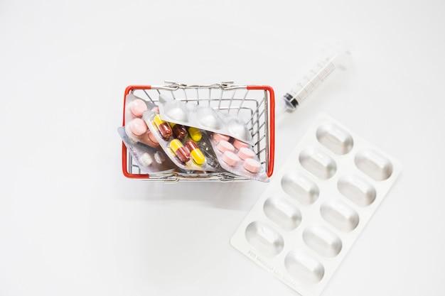 Medizinpillen verpacken im miniaturwarenkorb mit spritze auf weißem hintergrund
